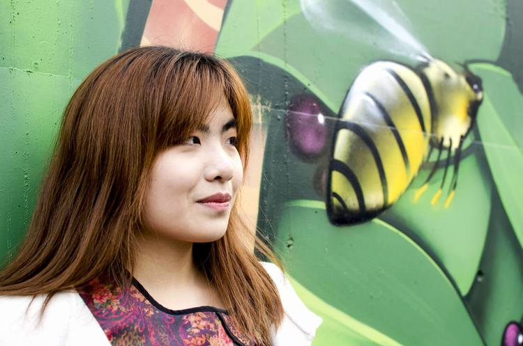 Photo of Belinda in front of street art with a bee