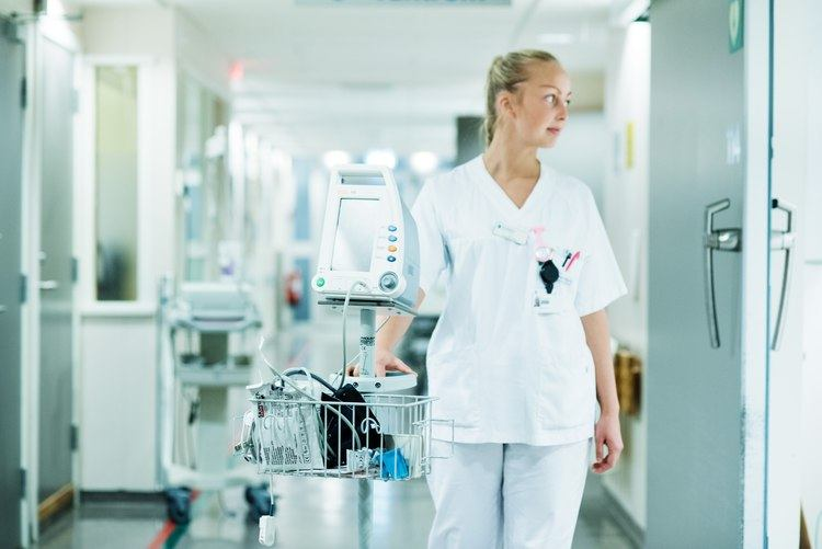 En sykepleiestudent triller en maskin i en sykehuskorridor.
