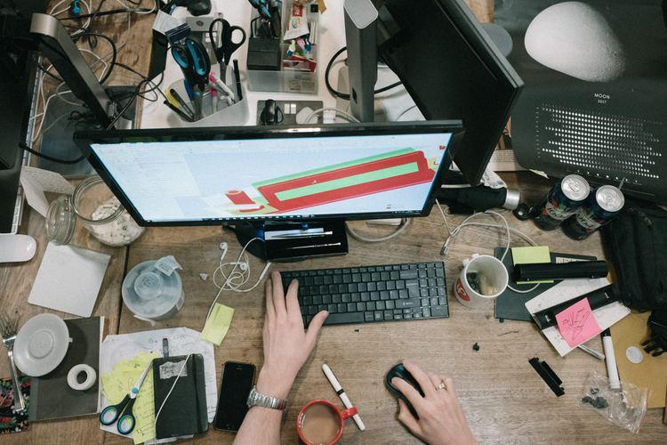 Overblikksbilde av en PC som står på en rotete pult.