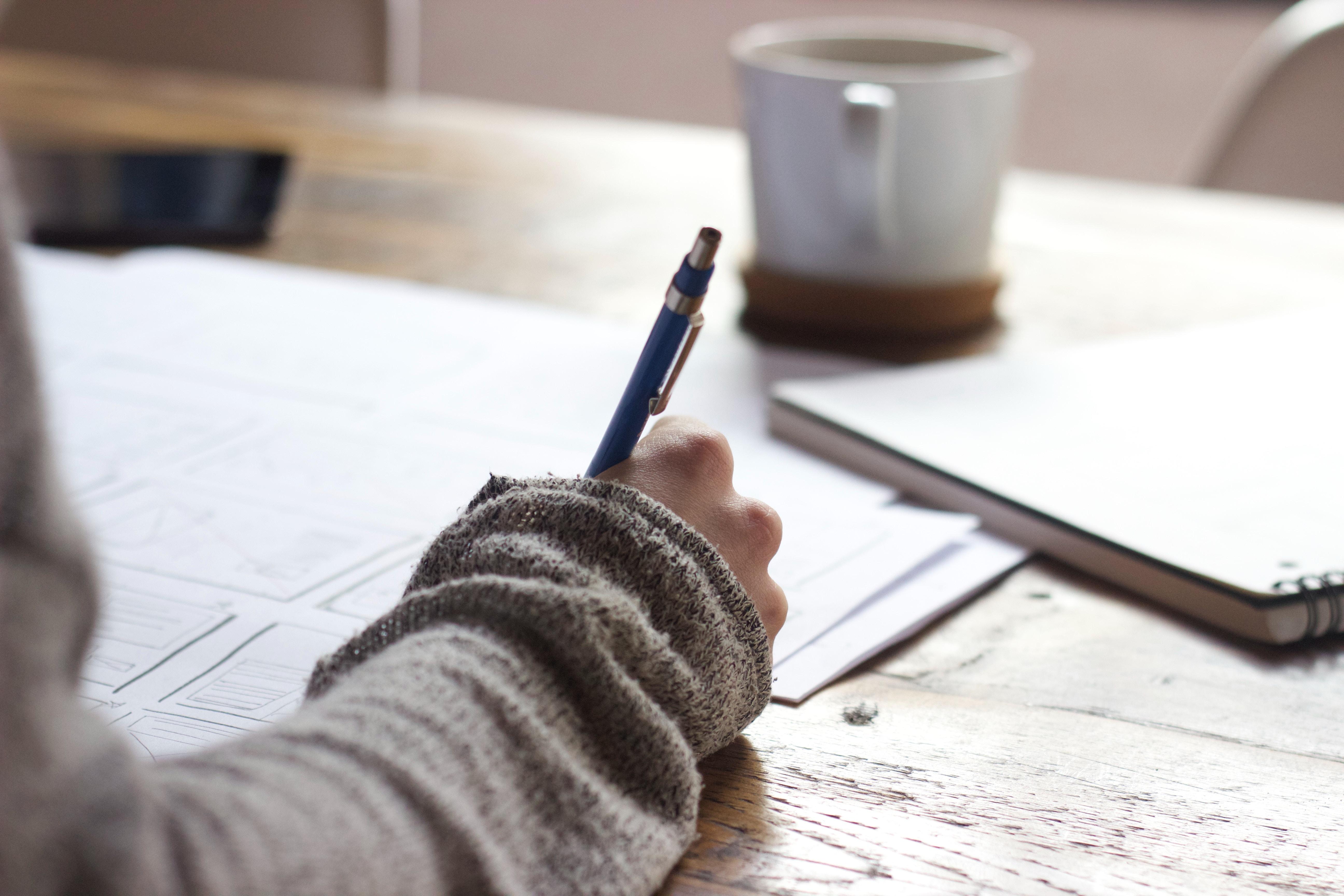 Hånd som skriver. Foto av Green Chameleon fra Unsplash.