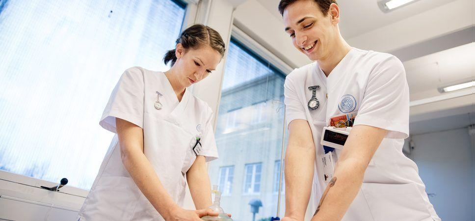 To sykepleiestudenter står ovenfor en annen student som spiller pasient. Studentene øver på hjerte- og lungeredning.