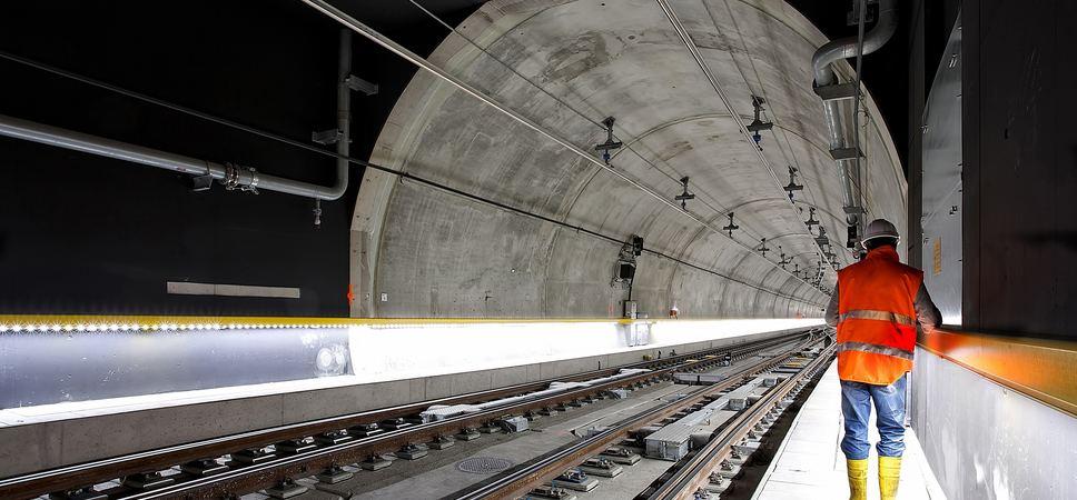 En mann i verneutstyr står og inspiserer en t-bane-tunnel.
